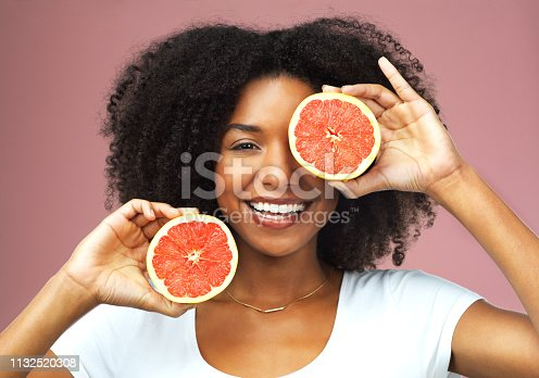 Studio shot of an attractive young woman covering her eye with slices of grapefruit against a pink background