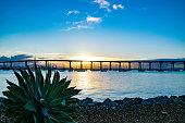 The sun rises by the San Diego Bay Bridge