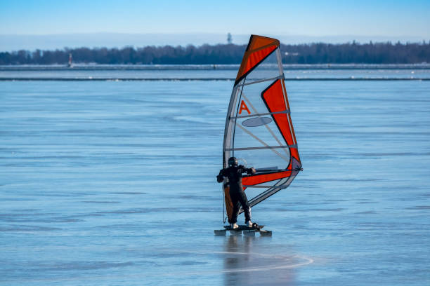 An alone surfer ice surfing on the frozen sea on a sunny spring day. stock photo