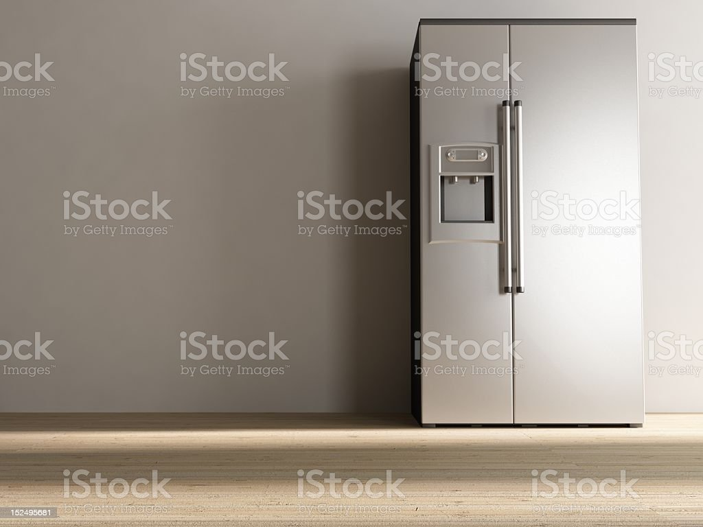 An aluminum refrigerator in front of a grey wall stock photo