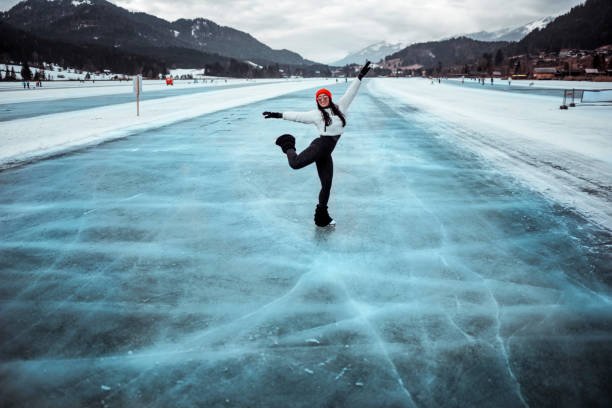 an amateur figure skater performing a spin on the surface of a frozen lake - skate liberdade gorro imagens e fotografias de stock