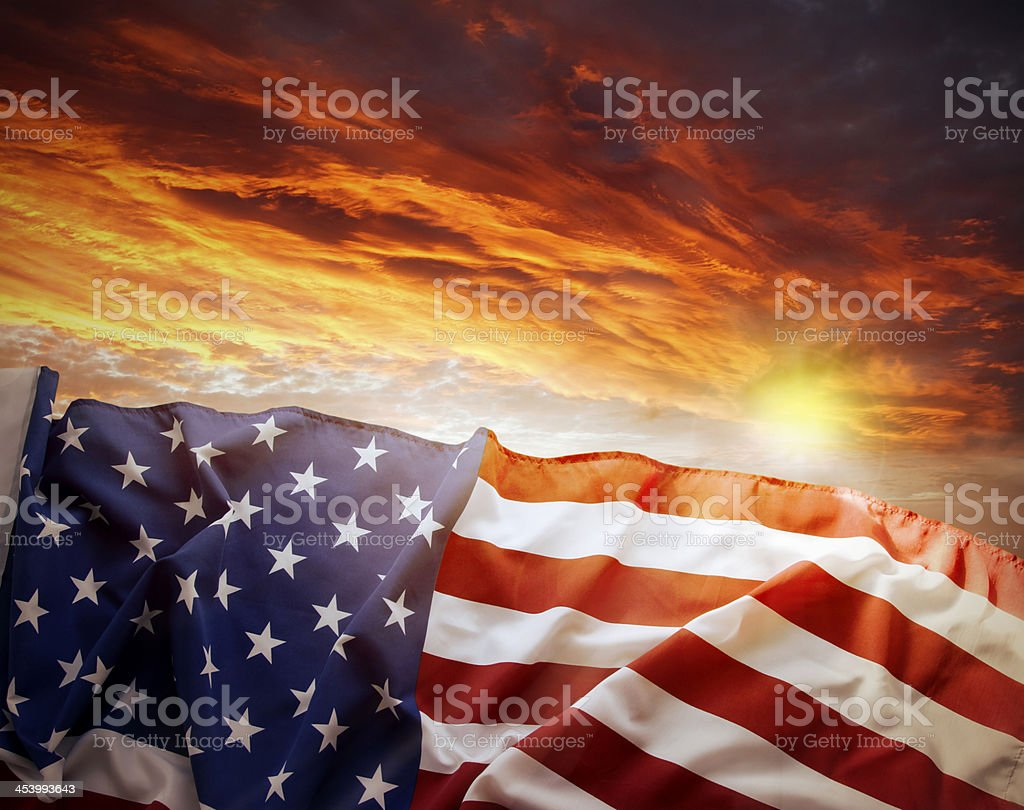 An American flag and a cloudy sunset stock photo