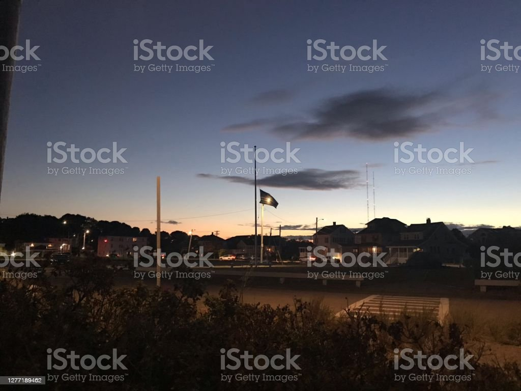 An American Flag at half mast Sunset An American flag at half mast for Ruth Bader Ginsberg  illuminated by a Streetlight with dark clouds overhead. American Flag Stock Photo
