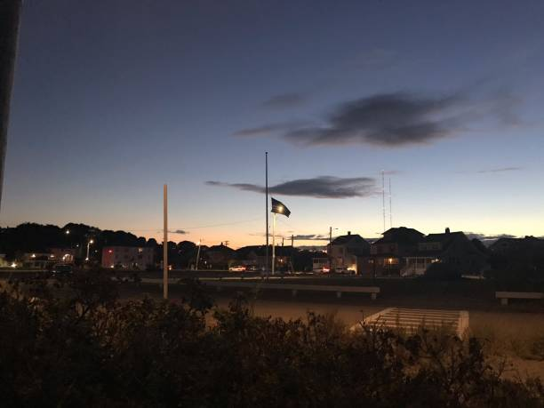 An American Flag at half mast Sunset An American flag at half mast for Ruth Bader Ginsberg  illuminated by a Streetlight with dark clouds overhead. ruth bader ginsberg stock pictures, royalty-free photos & images