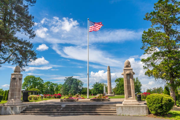 An American flag flies at the entrance to the Walnut Hill Park rose garden in New Britain, Connecticut. stock photo
