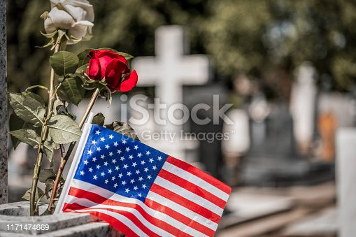 Memorial Day.Rose on tombstone. Red and White  roses on grave. Love - loss. Flower on memorial stone close up. Tragedy and sorrow for the loss of a loved one. Memory. Gravestone with withered rose