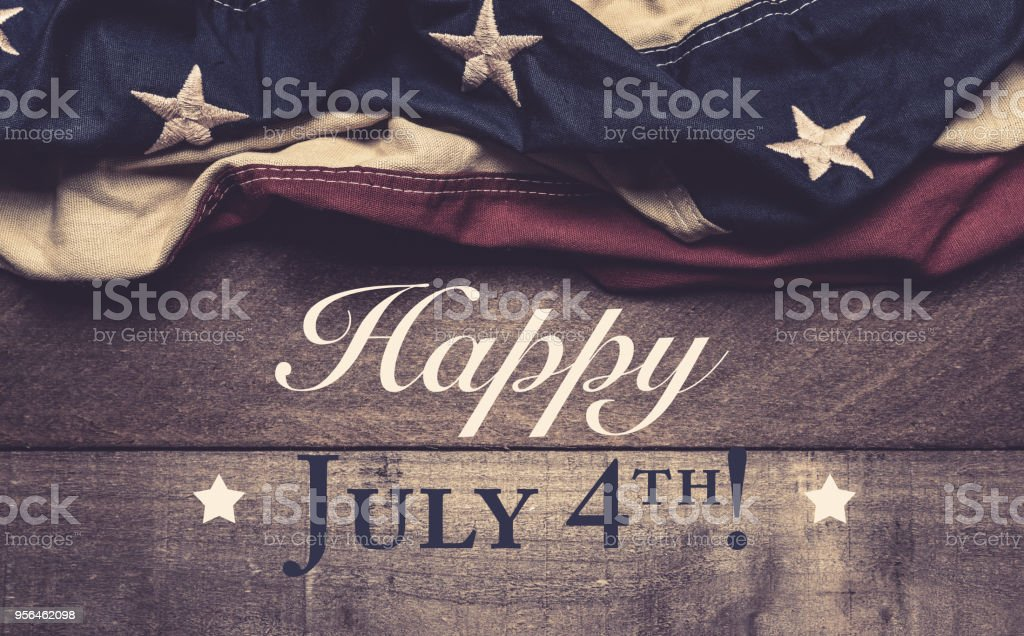 An American flag or bunting on a wooden background with July 4th greeting A vintage American flag or bunting on a wooden background with July 4th greeting American Culture Stock Photo