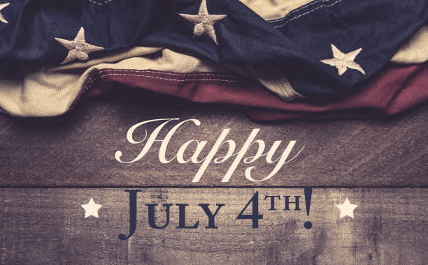 An American flag or bunting on a wooden background with July 4th greeting stock photo