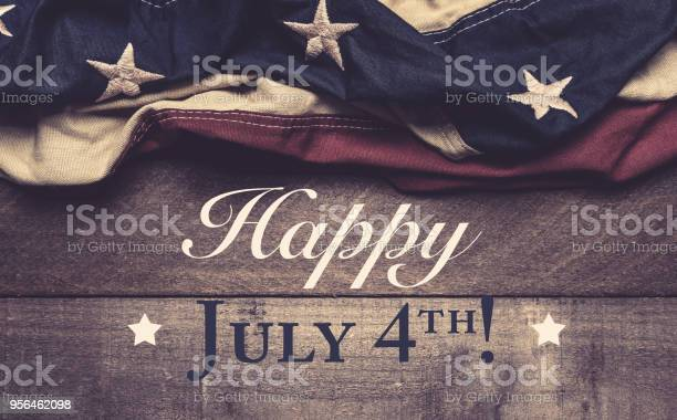 An American Flag Or Bunting On A Wooden Background With July 4th Greeting Stock Photo - Download Image Now