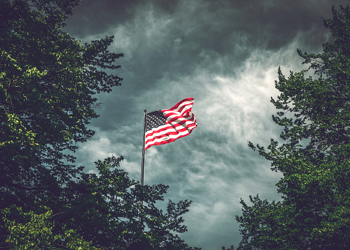 The American flag waving in the wind against the cloudy New York sky