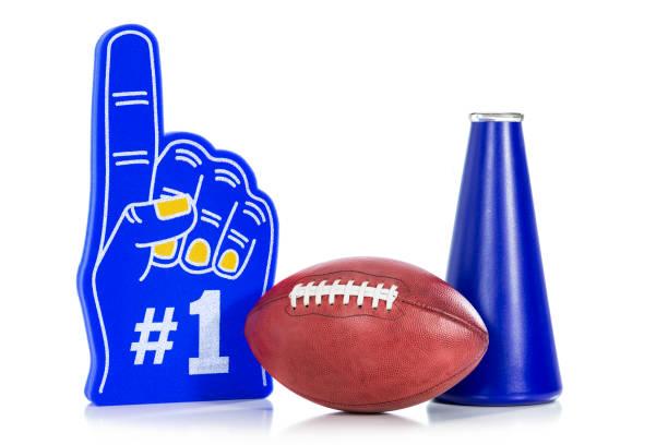 An American football with a blue #1 foam hand with yellow fingernails and megaphone against white background - foto stock