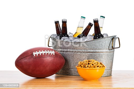 An American football sitting on a wood table next to a galvanized tub of assorted beer bottles in ice with a yellow bowl of pretzels against a white background.
