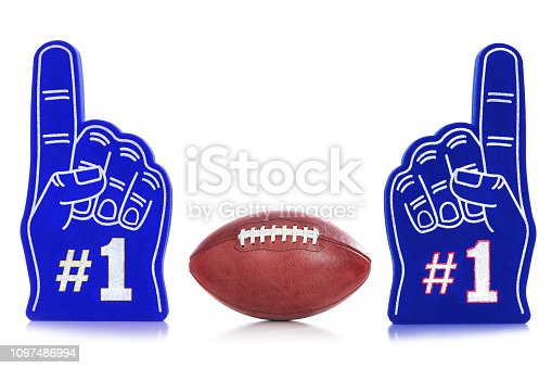An American football sitting between two #1 blue foam hands, one with yellow trim around #1 similar to a football team's colors and one with red trim around #1 similar to the other football team's colors sitting on a white background.