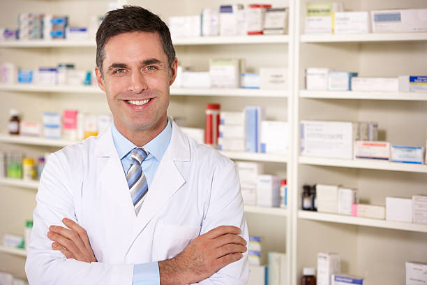 An American pharmacist at work standing in a white gown stock photo