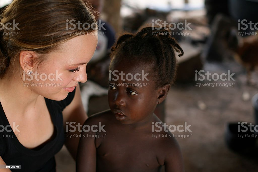 An American teenage girl with a young African girl stock photo