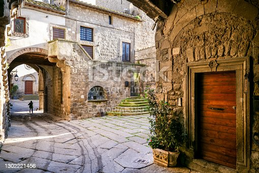 Viterbo, Italy, February 11 -- An ancient and suggestive alley with an arcade in the medieval quarter of San Pellegrino in the historic center of Viterbo, the capital of the ancient Etruscan region. This charming medieval town stands on the route of the ancient Via Francigena which in medieval times connected the regions of France to Rome up to the commercial ports of Puglia to reach the Holy Land. The medieval center of Viterbo is the largest in Europe, with countless historic buildings, churches and villages. Image in High Definition format.