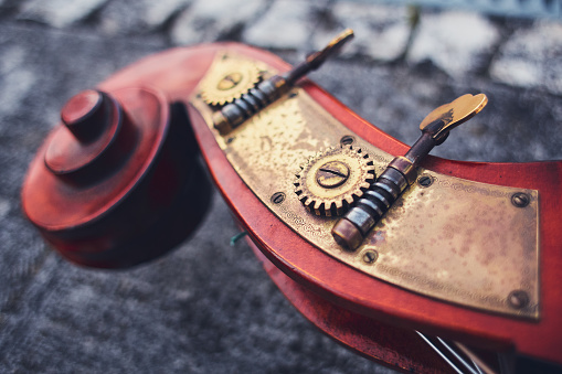istock An ancient detail of the cello of the Siz mahogany and brass details on the background of the old pavers. Wooden part of double bass, macro shot. Bronze brass bolts and gears on a musical instrument. 931274030