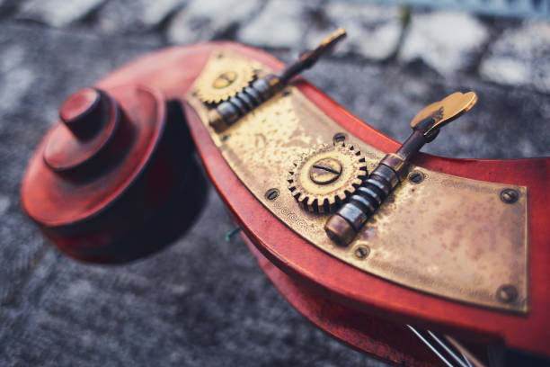 An ancient detail of the cello of the Siz mahogany and brass details on the background of the old pavers. Wooden part of double bass, macro shot. Bronze brass bolts and gears on a musical instrument. stock photo