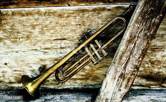 istock an ancient Jazz trumpet with a wooden background 1208415061