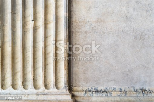 An ancient marble column with a portion of stone wall
