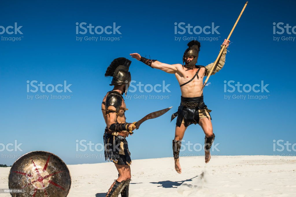 An ancient warrior with a spear in a jump attacks the Spartan stock photo