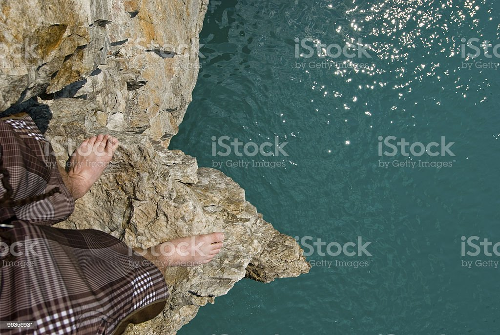 An angled shot of a man's feet on a cliff, right above water royalty-free stock photo