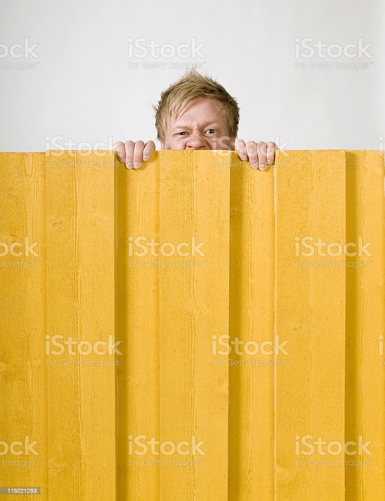 An angry man looking over a yellow fence  stock photo