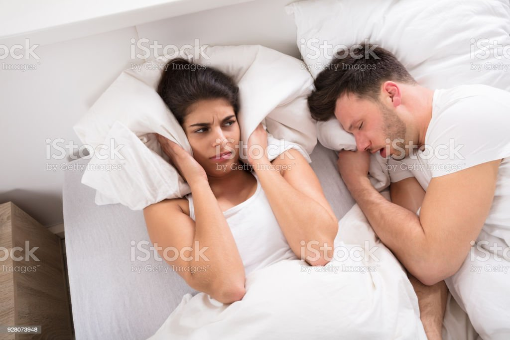 An Angry Woman With Snoring Husband On Bed stock photo
