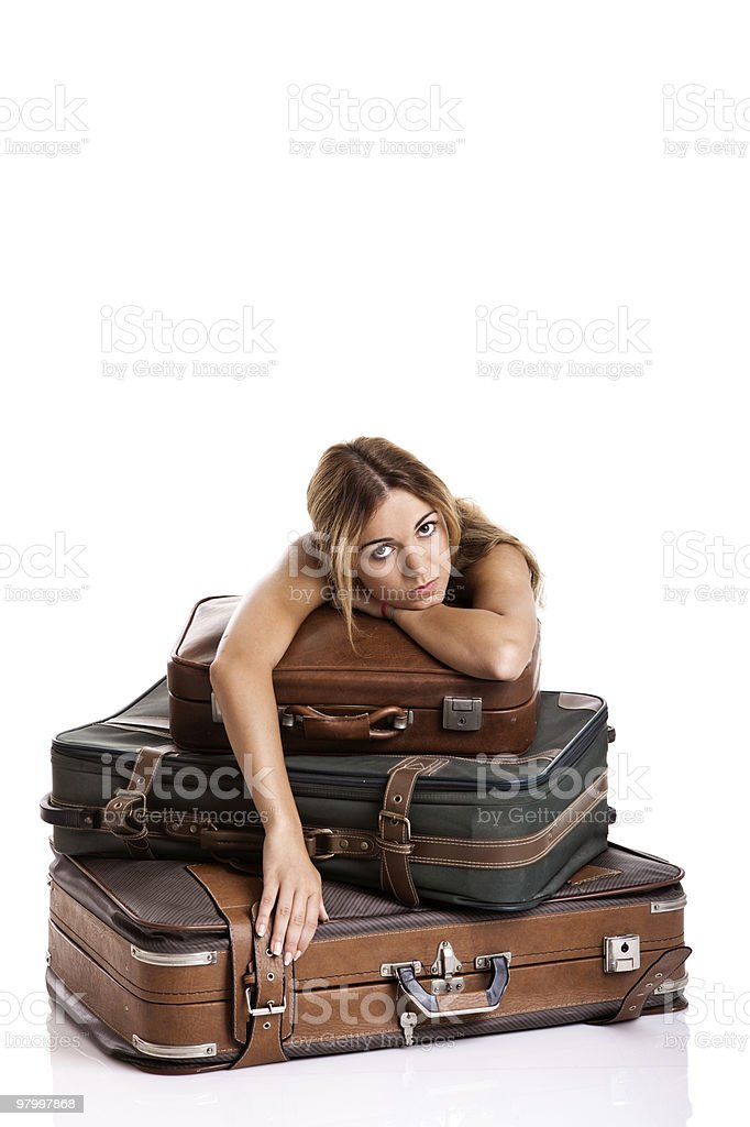 An annoyed woman resting on a stack of suitcases royalty free stockfoto