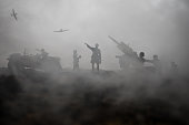 istock An anti-aircraft cannon and Military silhouettes fighting scene on war fog sky background. Allied air forces attacking on German positions. Artwork decorated scene. 1142581656