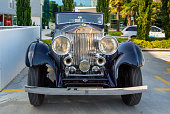 A antique car of Rolls Royce parked on a parking lot at dusk in Dubrovnik, Croatia.