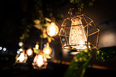 An antique lighting chandelier for decorate room interior with blurred bokeh of many lighting bulbs as backgound.