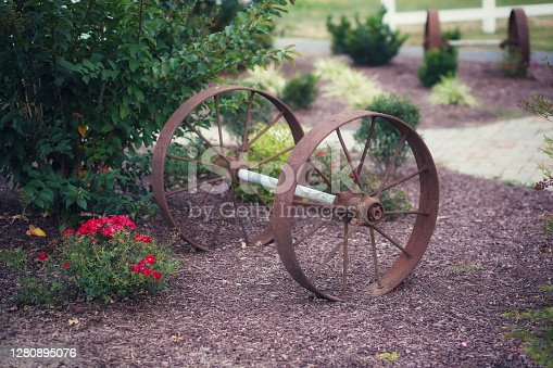 An antique metal  wagon wheel in a field