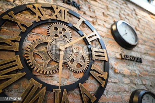 671883446 istock photo An antique roman clock on brick wall. 1251740286