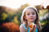 Little girl eating an apple. She is outdoors and looking at the camera, with apple juice on her face.