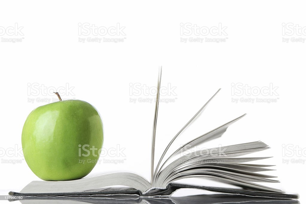 An apple resting on an open book, representing school royalty-free stock photo