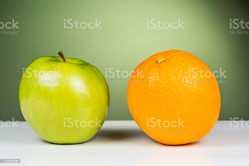 An apple sitting next to an orange stock photo