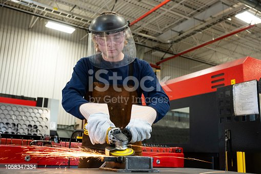 An industrial safety PPE topic.  An apprentice in a metal manufacturing factory wearing the correct protective workwear.