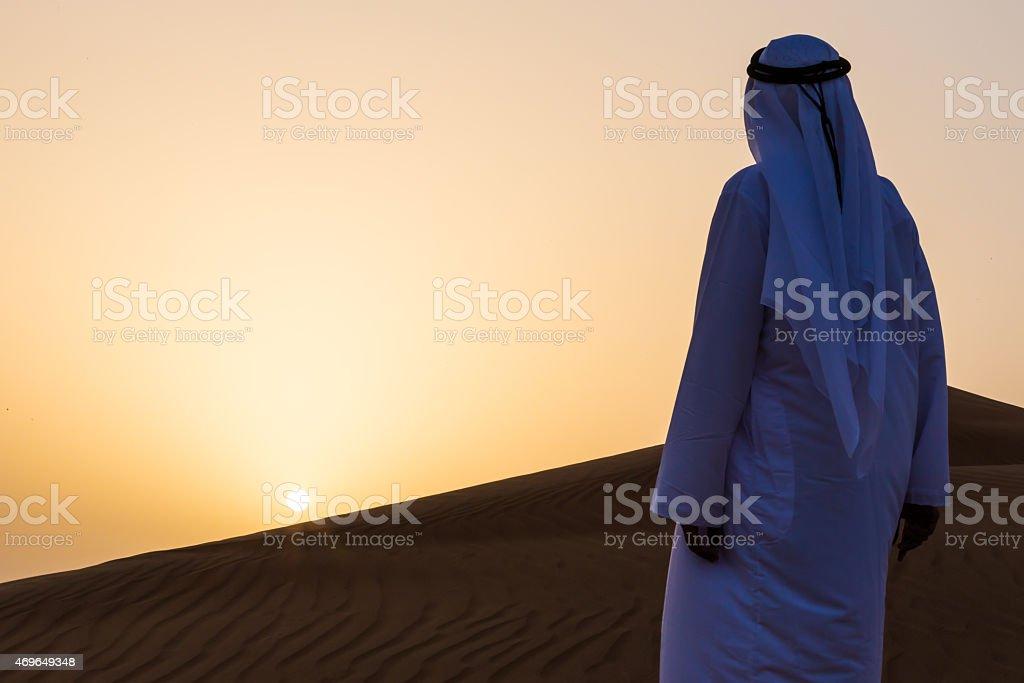 An Arab admiring the sunrise in desert, Dubai stock photo