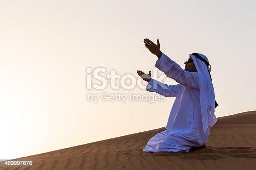 istock An Arab man praying in desert, Dubai 469997676