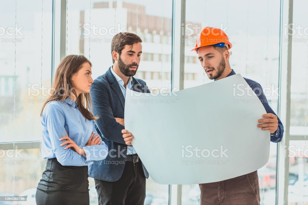 An architect in an orange box office is standing next to their...