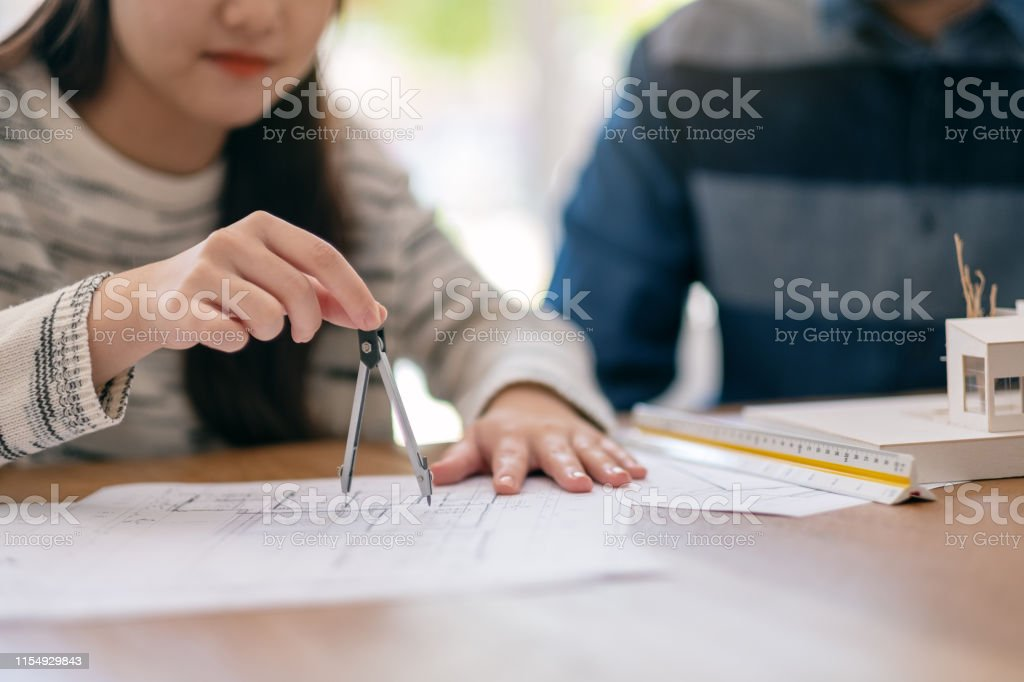 An architect using compass to draw and measure shop drawing in office