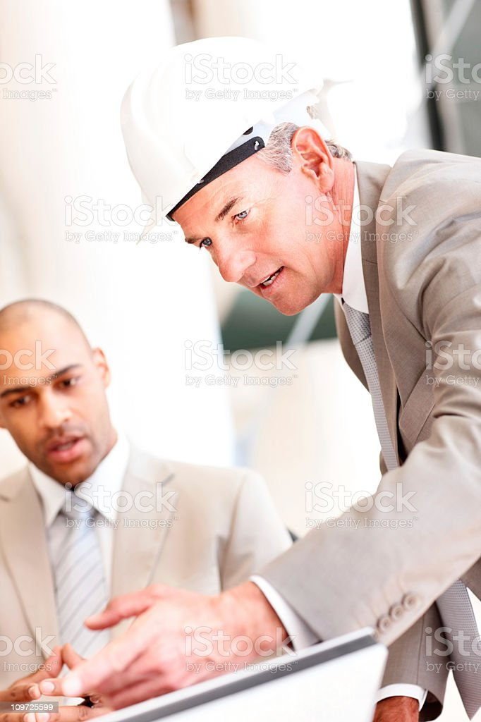 An architect wearing a helmet discussing his designs royalty-free stock photo