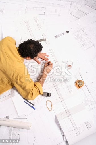 536971177 istock photo An architect working on a blueprint design  115917261