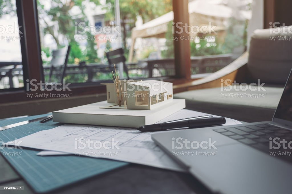 An architecture model with shop drawing paper and laptop on table in office  - Stock image .