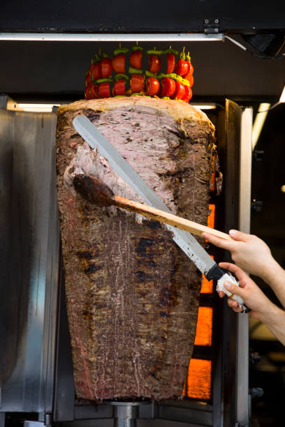 An arm moving to cut the kebab meat stock photo