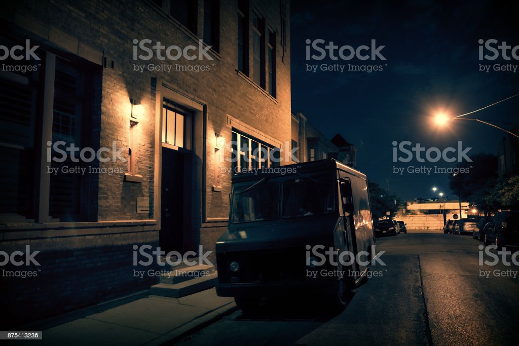 An armed security truck parked in a dark city street at night next to a building entrance. stock photo
