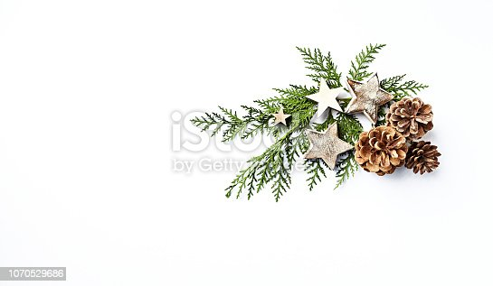 An arrangement of evergreen twigs, cones and Christmas decorations. Flatlay. Copy space. White background