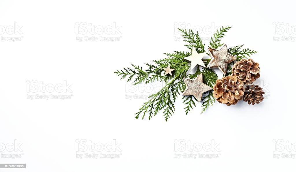 An arrangement of evergreen twigs, cones and Christmas decorations. Flatlay. Copy space. White background stock photo