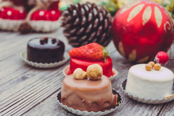 ein array von weihnachten desserts mit bunten, auf holzbrett - weihnachtsmannhüte aus erdbeeren stock-fotos und bilder
